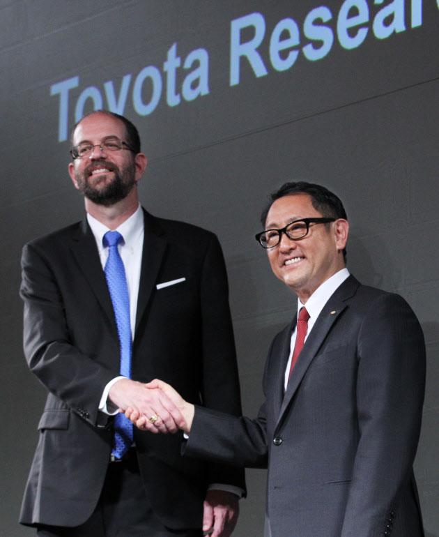 20160622_AI関連の新会社設立を発表し握手するトヨタ自動車の豊田章男社長(右)とギル・プラット氏(左)_日本経済新聞電子版